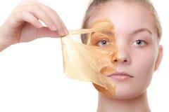 A mulher da menina em facial descasca fora a máscara. Cuidados com a pele. fotos de stock
