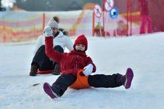 Mulher da menina da família que sledding na neve do monte do inverno foto de stock
