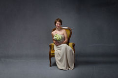Mulher da noiva que senta-se no sofá amarelo fotografia de stock
