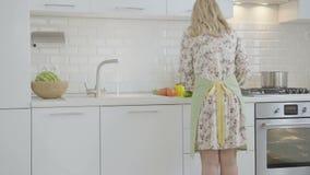 A mulher da opinião da parte traseira corta vegetais e água de fluxo video estoque