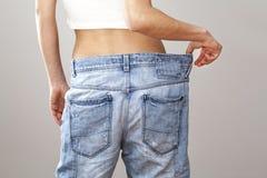 Mulher da perda de peso com blue-jeans foto de stock