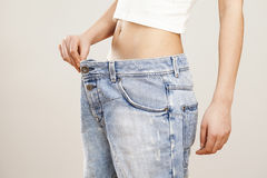 Mulher da perda de peso com blue-jeans fotografia de stock royalty free