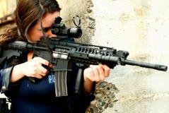 Mulher da polícia com injetor do assalto fotografia de stock