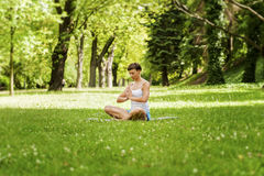Mulher da posição da ioga do zen na grama Imagens de Stock