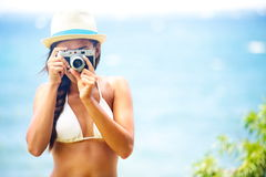 Mulher da praia do verão que guardara a câmera que toma a imagem Fotografia de Stock Royalty Free
