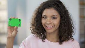 Mulher da raça misturada que guarda o cartão na cor verde, sorrindo, cuidados médicos, propaganda video estoque