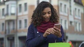 Mulher da raça misturada que verifica apps em linha da loja no smartphone moderno, comprando vídeos de arquivo