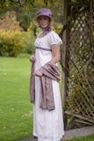 Mulher da regência nas caminhadas de creme do vestido e da capota em um jardim do verão imagem de stock royalty free