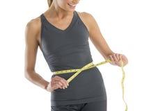Mulher da seção mestra que sorri ao medir sua cintura Fotos de Stock
