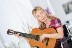 Mulher da senhora musican na cadeira de rodas que joga a guitarra em casa Foto de Stock Royalty Free