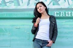 Mulher da sensualidade no t-shirt branco, no casaco de cabedal preto, na calças de ganga e no cabelo longo preto no ferro urbano  Fotografia de Stock