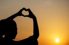 Mulher da silhueta da felicidade que faz a forma do coração Foto de Stock