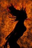 A mulher da silhueta no cabelo da genuflexão do biquini lançou no fogo Imagem de Stock