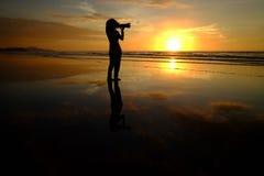 A mulher da silhueta toma a imagem no fundo do por do sol Fotografia de Stock Royalty Free
