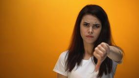 Mulher da virada que mostra os polegares para baixo, cliente descontentado com serviço, feedback filme