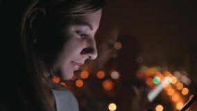 Mulher da vista lateral da noite que está à janela e aos usos Smartphone vídeos de arquivo