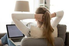 Mulher da vista traseira que relaxa com o portátil no sofá confortável em casa imagens de stock