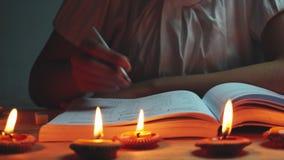 Mulher da zorra que lê um livro com a luz de muitas velas vídeos de arquivo