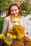 Mulher das pessoas de 55 anos no parque do outono com folhas coloridas Fotografia de Stock