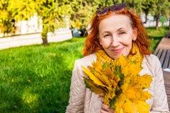 Mulher das pessoas de 55 anos no parque do outono com folhas coloridas Imagem de Stock