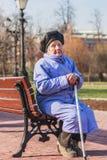 Mulher das pessoas de 89 anos que senta-se no banco Foto de Stock