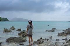 A mulher de Ásia que está na pedra pequena e tem a outra pedra em torno dela o mar e a nuvem e o céu azuis são fundo esta imagem  Imagem de Stock Royalty Free