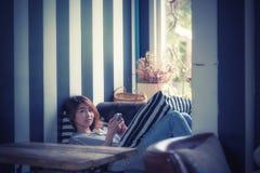 Mulher de Ásia que usa o telefone celular no sofá em sua casa foto de stock