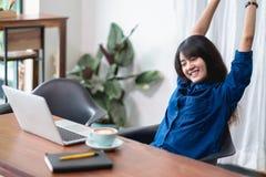 A mulher de Ásia relaxa após o trabalho, braço fêmea do aumento que estica acima dentro fotos de stock