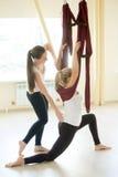 A mulher de ajuda do instrutor aéreo da ioga para fazer o ponto baixo investe contra a pose fotos de stock