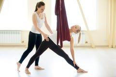 Mulher de ajuda do instrutor aéreo da ioga para fazer posição prolongada do triângulo fotos de stock royalty free
