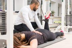Mulher de ajuda do instrutor com exercício dos músculos do pé fotos de stock