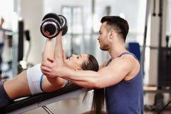 Mulher de ajuda do instrutor pessoal no gym Imagens de Stock Royalty Free
