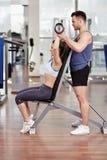 Mulher de ajuda do instrutor pessoal no gym imagem de stock royalty free