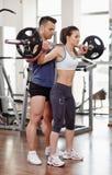 Mulher de ajuda do instrutor pessoal no gym fotos de stock royalty free