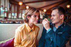 Mulher de alimentação de sorriso do homem com a colher no restaurante foto de stock royalty free