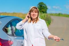 Mulher de 50 anos, chamando para um mecânico de carro pelo telefone Imagem de Stock