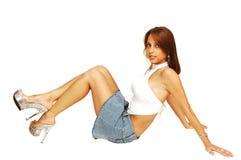 Mulher de assento na saia curta. fotos de stock royalty free