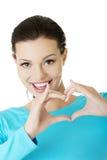 Mulher de Attractiveyoung que mostra o gesto do coração Fotos de Stock