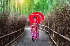 Mulher de bambu de Forest Asian que veste o quimono tradicional japonês na floresta de bambu em Kyoto, Japão imagem de stock royalty free