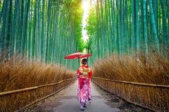 Mulher de bambu de Forest Asian que veste o quimono tradicional japonês na floresta de bambu em Kyoto, Japão fotos de stock royalty free