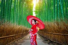 Mulher de bambu de Forest Asian que veste o quimono tradicional japonês na floresta de bambu em Kyoto, Japão imagens de stock