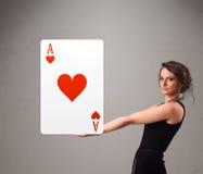 Mulher de Beautifu que guardara um ás vermelho do coração Foto de Stock