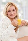 Mulher de Blondie com um vidro do sumo de laranja Foto de Stock