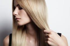 Mulher de Blondy que guarda seu cabelo fotografia de stock