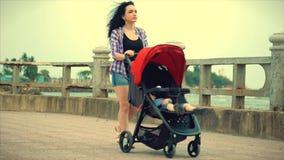 A mulher de Bueatiful em um dia de verão faz uma caminhada com um bebê, uma mãe nova anda ao longo da terraplenagem com um carrin vídeos de arquivo