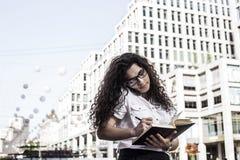 Mulher de Businnes que fala no telefone celular com cliente e verificações a programação em seu caderno imagens de stock