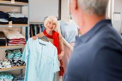 Mulher de cabelo cinzenta adorável que aceita cumprimentos do vendedor a respeito de seu vestido escolhido foto de stock