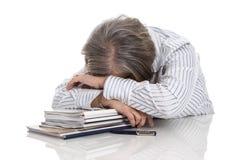 Mulher de cabelo cinzenta que dorme em livros - sobrecarregado isolado no whi imagem de stock royalty free