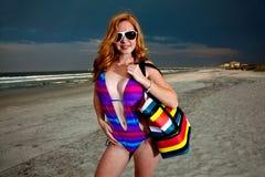 Mulher de cabelo consideravelmente vermelha dos jovens que joga em uma praia Foto de Stock