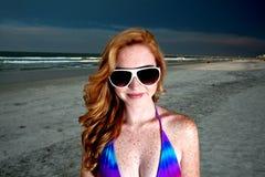 Mulher de cabelo consideravelmente vermelha dos jovens que joga em uma praia Fotos de Stock Royalty Free